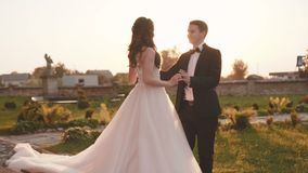 Lovely groom comes to bride and caresses her at castle stock footage