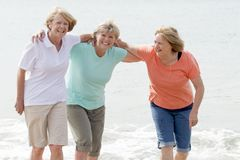 Lovely group of three senior mature retired women on their 60s having fun enjoying together happy walking on the beach smiling pla Stock Photo