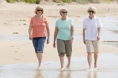 Lovely group of three senior mature retired women on their 60s having fun enjoying together happy walking on the beach smiling pla Stock Photography