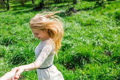 Lovely happy blonde with flying hair holding my hand and dancing around in blossom garden. Point of view Stock Photos