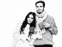 Lovely happy couple holding cups. Lovely cute happy couple holding colorful cups. Bearded caucasian men with moustache in knitted blue sweater and scarf with stock image