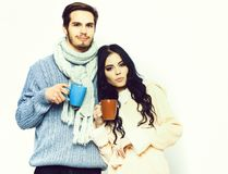 Lovely happy couple holding cups. Lovely cute happy couple holding colorful cups. Bearded caucasian men with moustache in knitted blue sweater and scarf with royalty free stock photography
