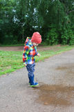 Lovely happy little boy in wellingtons walking after rain Royalty Free Stock Images
