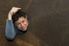 Lovely and happy man, inside brown iron plate, pointing a space for an advertisement and commercial project. Copy space stock photo