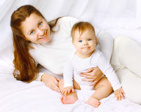 Lovely happy mom and baby having fun in bed Royalty Free Stock Images