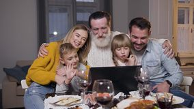 Attractive different generation family having video chat on computer during festive dinner and greeting their