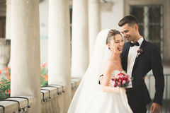 Lovely happy wedding couple, bride with long white dress posing in beautiful city Royalty Free Stock Photo