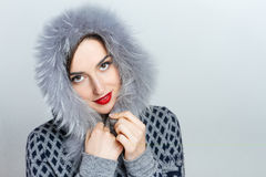 Lovely Happy Woman. Merry Christmas. Girl in good winter sweater with hood. Nice emotional young  on a gray background Stock Photo