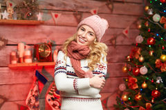 Lovely Happy Woman. Merry Christmas. Young female wearing warm clothes, cosy sweater, hat and scarf, smiling over christmas tree decorations stock photography