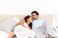 Lovely hispanic couple relaxing in their bedroom Stock Images