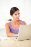 Lovely hispanic woman looking displeased at work Royalty Free Stock Photography