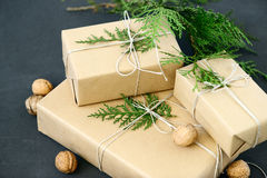 Lovely Holiday wrapping ideas rustic eco Christmas packages with brown paper, string and natural fir branches on dark background Stock Image