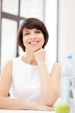 Lovely housewife with green apple and bottle of water Royalty Free Stock Images