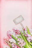 Lovely Hyacinths flowers  with bokeh and blank wooden sign on pink background, top view. Springtime and gardening Stock Photos