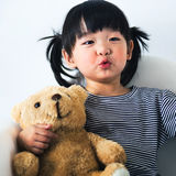 Lovely and innocent asian kid playing with teddy happily Royalty Free Stock Images