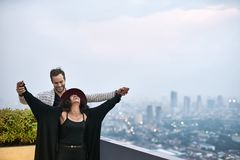 Lovely interracial couple on balcony. Laughing interracial couple on the balcony on the background of the cityscape. Black girl wears dark clothes and a crimson Royalty Free Stock Photography