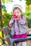 Lovely kid with candy outdoors. Smiling while holding candy. royalty free stock photography