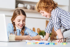 Lovely kid distracting his sister from doing homework Royalty Free Stock Photography