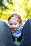 Lovely kid girl sitting on father legs outdoors royalty free stock photography