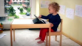 Lovely kid playing with tablet pc sitting on small chair near table. stock video