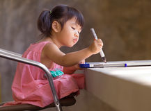 Lovely kid practice for writing on white broad before class lear Royalty Free Stock Images
