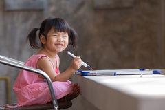 Lovely kid practice for writing on white broad before class lear Stock Photography