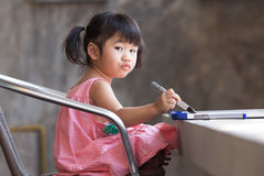Lovely kid practice for writing on white broad before class lear Royalty Free Stock Image