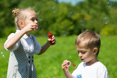Lovely kids blow bubbles in the park Royalty Free Stock Image