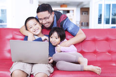Lovely kids with dad using laptop on sofa Stock Photos