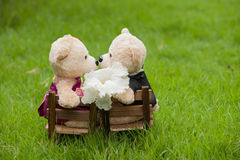 Lovely kiss teddy bear sit on wooden chair, Concept wedding of l Stock Photo