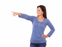 Lovely lady pointing to her right while standing Stock Photo