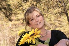 Lovely lady poses outdoors holding sunflowers. Lady offers a lovely smile as she holds bright sunflowers for her pose Stock Photos