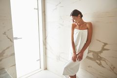 Lovely lady smiling and closing her eyes while standing in white towel stock photos