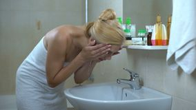 Lovely lady washes face in front of mirror, satisfied after visiting cosmetician. Stock footage stock video footage