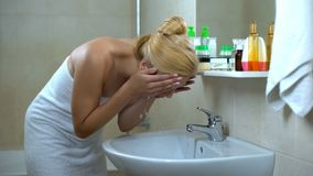 Lovely lady washing face in front of mirror, satisfied after cosmetician visit. Stock photo royalty free stock images
