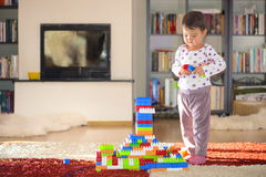 Lovely laughing little child, brunette girl of preschool age playing with colorful blocks sitting on a floor. In a sunny room with a big window at home or royalty free stock photo