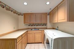 Lovely laundry room interior with wooden cabinets. royalty free stock photography