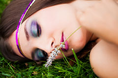Lovely lavender. Portrait of a pretty brunette model resting in the green grass smelling picked lavender wearing a purple and gold sequined headband stock photos