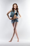 Lovely leggy girl posing in jeans costume Royalty Free Stock Image