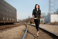 Lovely Lithe Model Running Along Train Tracks. An image of a young model wearing a leather jacket and leather pants, running along train tracks Royalty Free Stock Photos