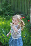 Lovely little blond little girl blowing a dandelion and making a wish in summer day Stock Photo