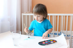 Lovely little boy age of 2 years with brush and paints at home Stock Photography