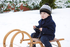 Lovely little boy on ancient sledge on winter day Royalty Free Stock Images