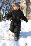 Lovely little boy in black snowsuits running in winter Stock Images