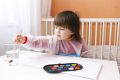 Lovely little boy with brush and water color paints at home Royalty Free Stock Images