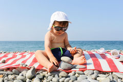 Lovely little boy building pebbles tower on the beach Royalty Free Stock Images