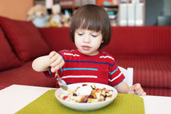 Lovely little boy eats fruit salad Stock Images