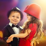 Lovely little boy and girl dancing. In lights of the city. Love, friendship concept Stock Photos