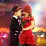Lovely little boy giving  a rose to girl. Lovely little boy giving a rose to fashionable girl and her excited Royalty Free Stock Image