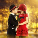 Lovely little boy giving  a rose to girl. Lovely little boy giving a rose to fashionable girl and her excited. Love concept Stock Photos